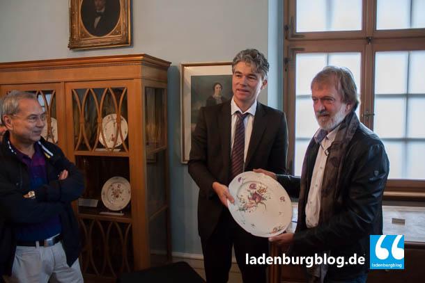 Hans Wilser (rechts) übergibt Dr. Andreas Hansen ein altes Familienerbstück.